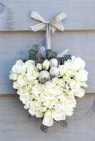 White rose heart wreath with speckled eggs tied to wall