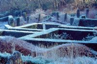 View over the Yew Garden to the Wild Garden and wood from the Grasses Parterre, Beech hedge in foreground - Veddw House Gardens, February