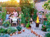 People using dining area, gravel pathway lit with candles, container plants include vegetables and herbs