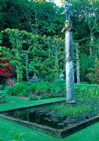 Pleached limes and pool with statue of Centurion. Rhododendron 'Gwilt King' and Primula - Plas Brondanw
