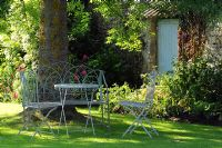 Garden table and chairs in the shade on a summer evening