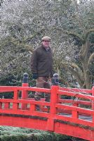 Owner Guy Rasch standing on the red Japanese bridge, Heale House Gardens, Wiltshire