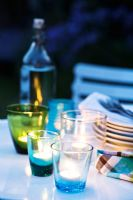 Nightlights in glass holders on garden table