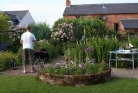 Man cooking at barbeque on patio in country garden with adjacent eating area, herbaceous borders, trellis with climbing roses and a circular bed with Cosmos and Allium