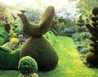Topiary bird and view of topiary garden, lawn path leading to formal pond - Charlotte Molesworth's garden, Kent
