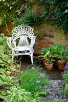 Cliff Hill - Top part of garden with chair rescued from skip. Plants include variegated sage, Allium schoenaprasum - chives, Aubrietia, Heuchera
