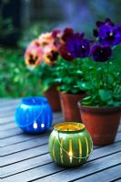 Pansies in terracotta pots on a wooden garden table with tealights in the foreground