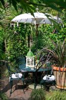 An ornate parasol casts shade on a secluded seating area surrounded by dense climbers and striking foliage plants in pots