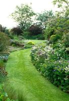 Mown strip of lawn takes a curving path along the colourful border towards the front door.