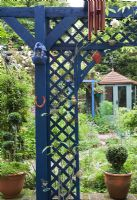 Overview of small densely planted courtyard garden looking through blue trellis to green painted summerhouse.