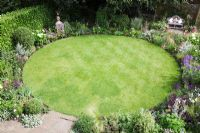 Overview of small Urban garden packed full of plants simply designed around a central circular lawn