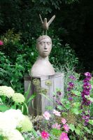 Small urban garden packed full of plants. Sculpture by Christopher Marvell on oak plinth, surrounded by Hydrangea arborescens 'Annabelle', Cosmos bipinnatus 'Sensation', Malva sylvestris 'Mauritanicus' and Allium seedheads.