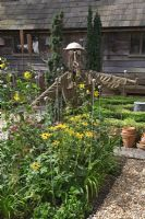 Seaside Inspired garden. The yellow garden with scarecrow made from a colander, cutlery and old pitchfork. Helianthus, Rudbeckia, Echinops, Cosmos and Fennel growing in border. Small Box - Buxus parterre by rustic beach hut and Taxus - Yew columns behind.