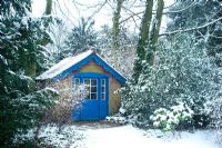 Summer house with blue woodwork in snow