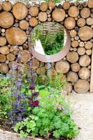 Detail of Moongate in recycled log wall with border of Geranium sylvaticum 'Narratives of Nature' garden at Future gardens, St Albans, Herts