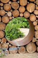 Detail of Moongate in recycled log wall. 'Narratives of Nature' garden at Future gardens, St Albans, Herts