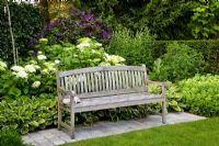 Wooden bench backed by a border of Hosta, Hydrangea arborescens 'Annabelle' and Clematis viticella 'Etoile Violette'