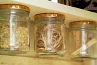 Glass jars with pegs and twine - jar lids are stuck to top of shelf