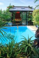 Mediterranean style garden with swimming pool and glass summerhouse