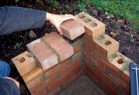 Building a barbeque. Step 7 of 11. On the side walls add bricks side on to provide support for the barbeque tray