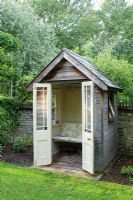 Small timber summer house with bench seat, french doors, painted wood panelling and slate roof. Made by the owner from an old garden shed and architectural salvage materials.