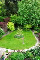 View of neatly kept garden with Sorbus aucuparia in flower, Magnolia underplanted with tulips, stone bird bath, mixed shrubs chosen for their coloured foliage including Philadelphus, Sambucus and Acer