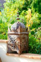 Moroccan pierced ironwork candle lantern on wall