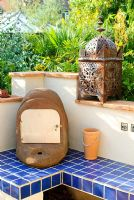 Outdoor oven on blue tiled plinth with Moroccan candle lantern on wall