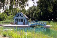 Natural swimming pool which is rain water fed, water lilies, reed filter beds, decking, bridge and gazebo