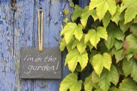 Slate sign on door, reading 'I'm in the garden'