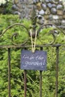 Slate sign on wrought iron gate, reading 'I'm in the garden'