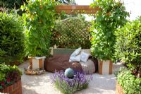 Seating area in vegetable garden with Lavandula 'Hidcote' surrounding a solar-powered water feature and Runner Beans in pots. 'Food for Thought' - Silver Gilt Medal Winner - RHS Hampton Court Flower Show 2010