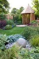 Stone water feature, plantings of Hosta and Stipa tenuissima with gazebo in background - The Urban Retreat, Bronze medal winner at RHS Hampton Court Flower Show 2010