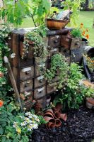Potting and sowing area with rustic chest of drawers - RHS Tatton park flower Show 2010