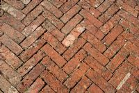 Herringbone block paving as garden path, made from old red bricks