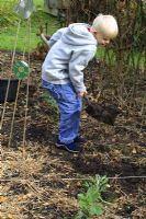 Leonie Woolhouse's grandson, Arthur, learning how to dig in the vegetable garden - The Old Sun House, Wymondham, Norfolk, NGS