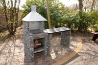 Barbeque made of gabions on patio - Appeltern garden, Holland
