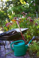 Replacing plants, organic compost in wheelbarrow, spade and watering can
