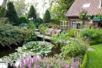 Pond with seating area, Astilbe chinensis 'Pumila' in foreground