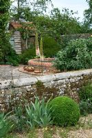 Front garden with stone wall and gravel path, with Eremurus and Buxus - Box balls. Sandhill Farm House, Hampshire.