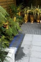 Small urban courtyard garden with Phormium in containers and uplighting