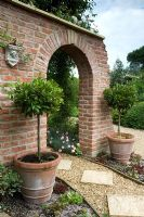 Brick wall with arch and pots with standard Laurus nobilis - Bay trees. Dianthus edging diagonal stepping stone path. Parsons Cottage
