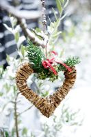 Heart shaped wicker wreath with yew foliage, ivy berries and red berries