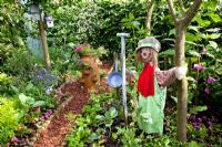 Vegetable garden for children with scarecrow and bark chipping path