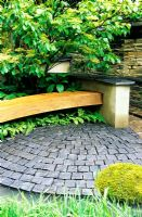 Wooden bench underplanted with ferns and Cornus contoversa 'Pagoda' in courtyard garden with stone paving setts - A Garden for Robin, designed by students at Leeds Metropolitan University 2006 RHS Chelsea Flower Show
