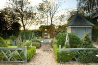 Buxus - Box parterre with water feature, wooden shed and topiary. Silverstone Farm, Norfolk, October