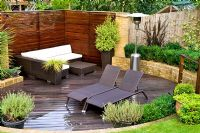 Decked patio with modern furniture and patio heater in urban garden. Lavandula - Lavender in containers. Muswell Hill, London