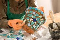 Decorating a terracotta pot with mosaic pieces