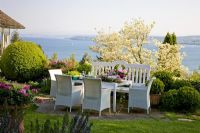 Table and chairs, planting of Buxus, Cornus, Pelargonium and Rosmarinus, overlooking the lake of Constance, Germany