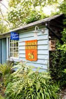 Wooden garden building with old enamel signs - Helen Riches' Garden, Essex